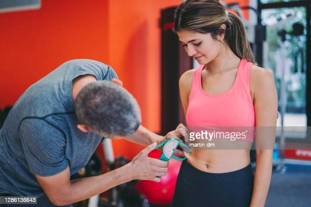 coach measuring woman's body fat with caliper - skin fold calliper stock pictures, royalty-free photos & images