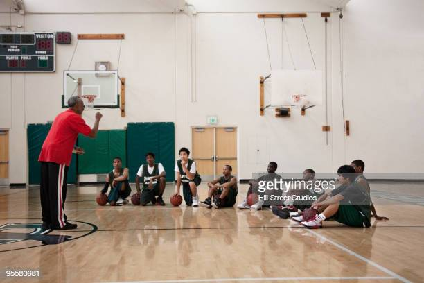 Coach meeting with basketball team in gym