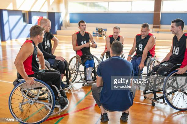 coach meeting with wheelchair basketball team in gymnasium - competition group stock pictures, royalty-free photos & images