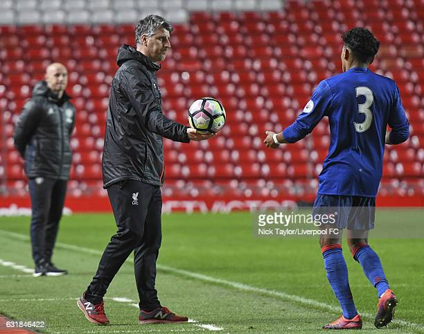 U23 coach Mick Garrity of Liverpool hands the ball to Demitri Mitchell of Manchester United for a throwin during the Liverpool v Manchester United...