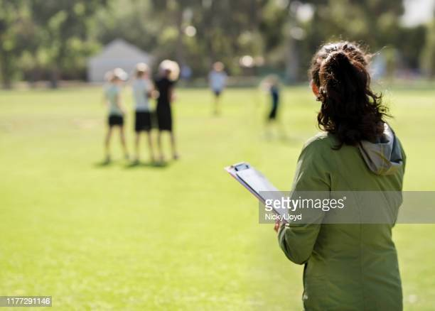 coach monitoring the team practicing - checking sports stock pictures, royalty-free photos & images