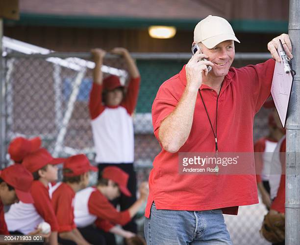 Coach on cell phone, boys (9-11) in baseball dugout in background