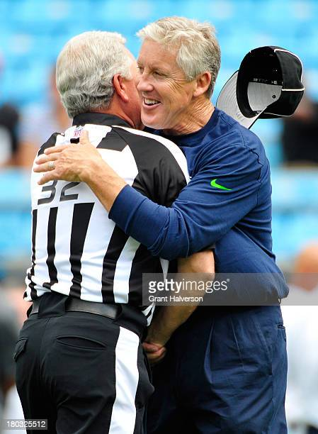 Coach Pete Carroll of the Seattle Seahawks embraces NFL official line judge Jeff Bergman before a game against the Carolina Panthers at Bank of...