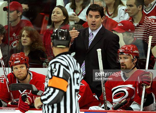 Coach Peter Laviolette of the Carolina Hurricanes argues with referee Dan O'Halloran against the Buffalo Sabres in game two of the Eastern Conference...