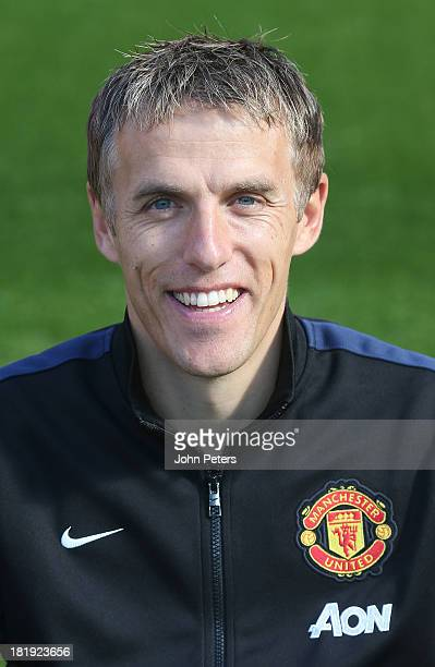 Coach Phil Neville of Manchester Unted poses at the annual club photocall at Old Trafford on September 26 2013 in Manchester England