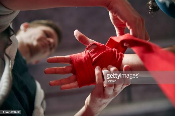 Coach preparing teenage girls boxing hand wraps