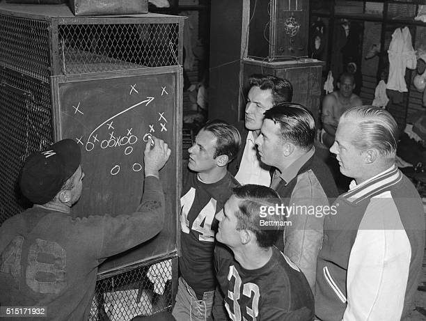 Coach Ray Flaherty of the Washington Redskins plotting plays on the blackboard during a skull drill Nov 29 Players looking on are Sammy Baugh passing...