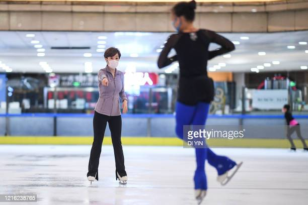 A coach reacts during a training session with a protective mask on May 29 2020 in Beijing China A free figure skating class was held in an ice sports...