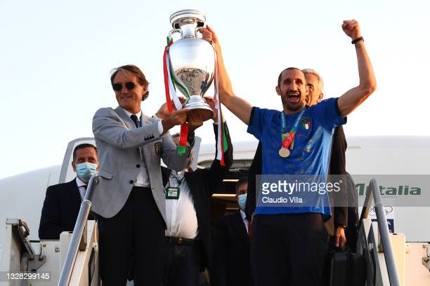 Coach Roberto Mancini and captain Giorgio Chiellini lift The Henri Delaunay Trophy after travelling back to Rome following the Euro 2020 victory on...