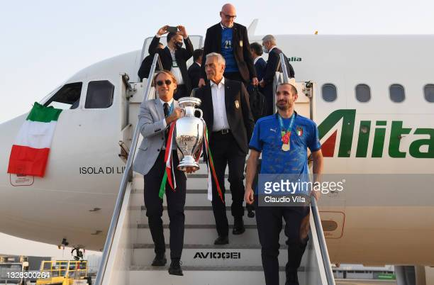 Coach Roberto Mancini, FIGC president Gabriele Gravina and captain Giorgio Chiellini walk down the airplane stairs with The Henri Delaunay Trophy...