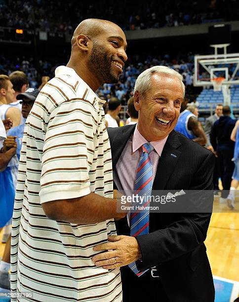 Coach Roy Williams of the North Carolina Tar Heels hugs former player Vince Carter during Late Night with Roy, the first practice of the basketball...