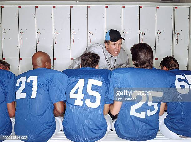 coach shouting at american football players in locker room - pep talk stock pictures, royalty-free photos & images