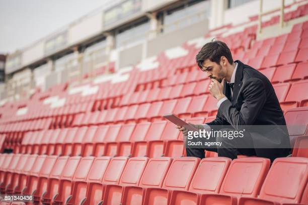 Coach sitting on the bleachers