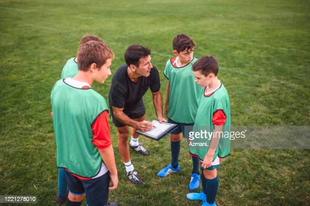 entrenador sketching notas de juego para boy footballers on field - campamento de entrenamiento deportivo fotografías e imágenes de stock