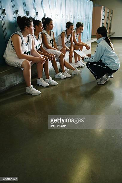 Coach speaking to female basketball team in locker room
