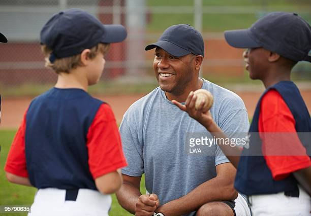coach speaking with little league team - little league stock pictures, royalty-free photos & images