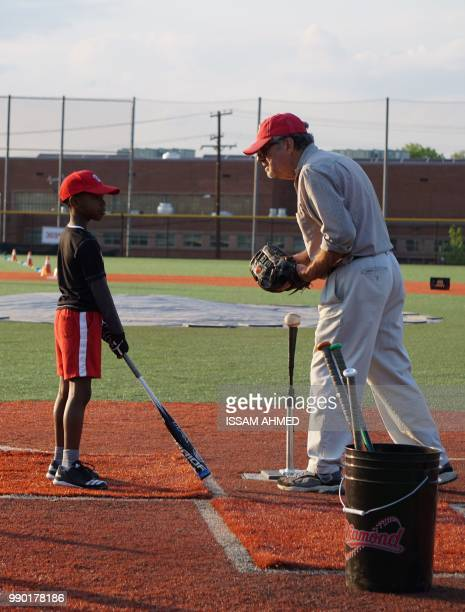 A coach speaks with a boy as he practices baseball skills at the Nationals Youth Baseball Academy in Washington DC on May 7 2018 On a searing hot...