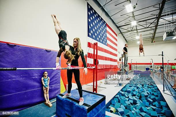 Coach spotting gymnast on bars during training