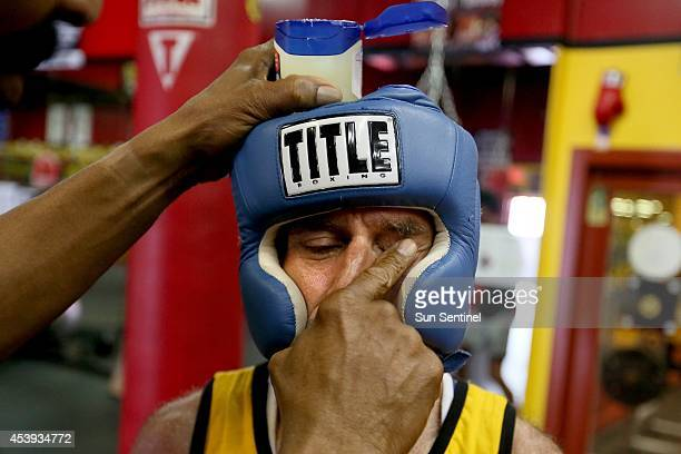 Coach Stacy McKinley applies vaseline to Rick Picone's face before his sparring match at Gold's Gym in Deerfield Beach Fla on Monday Aug 11 2014