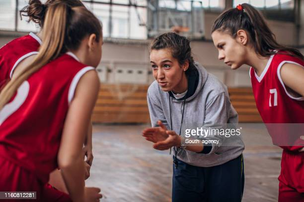 coach standing with basketball team - coach stock pictures, royalty-free photos & images