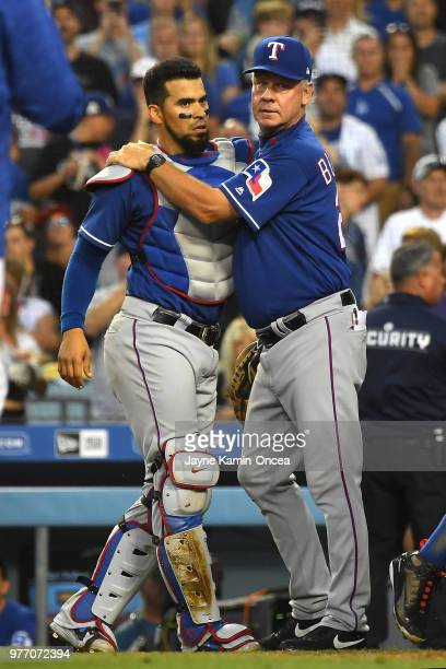 Coach Steve Buechele holds on to Robinson Chirinos of the Texas Rangers after he and Matt Kemp of the Los Angeles Dodgers came to blows after a...