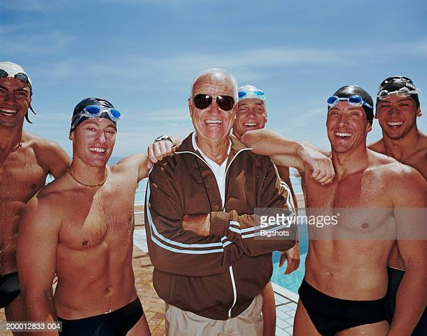 coach surrounded by group of male swimmers, portrait - old man in speedo stock photos and pictures