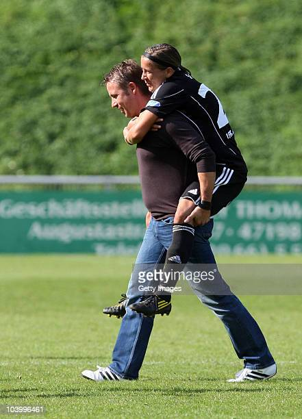 Coach Sven Kahlert of Frankfurt carries one of his players Sandra Smisek after the Women's Bundesliga match between FCR Duisburg and FFC Frankfurt at...
