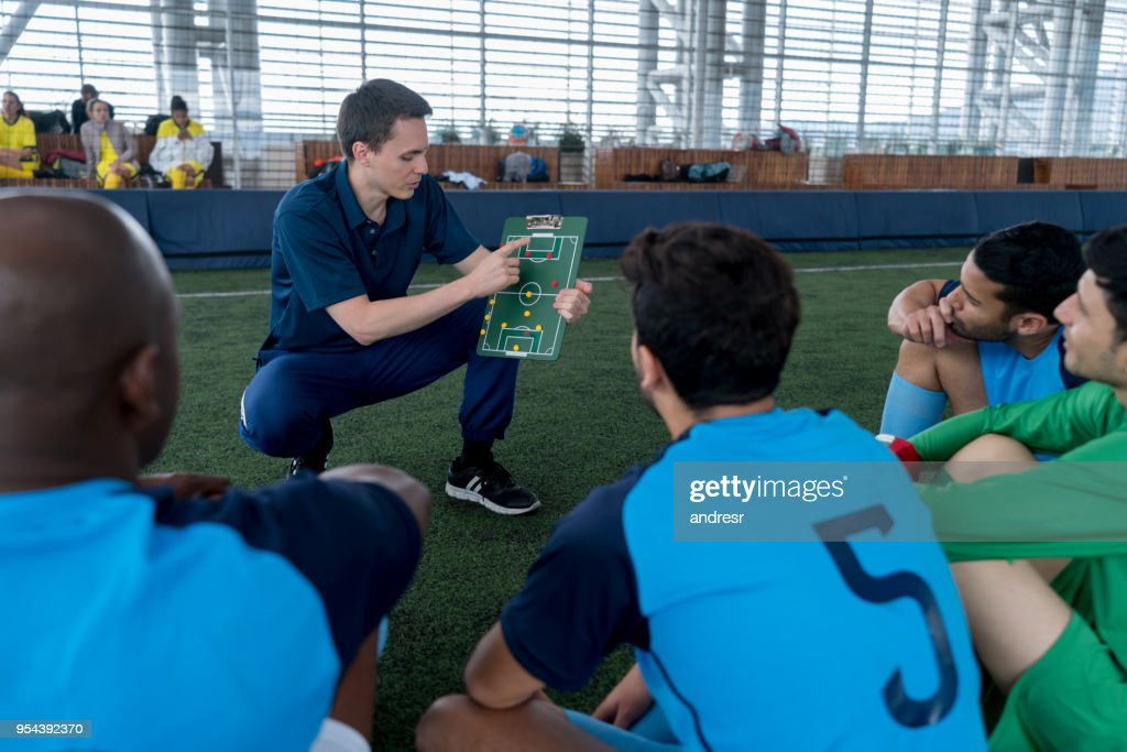 Coach talking about strategy to his players pointing at a clipboard with magnets : Stock Photo