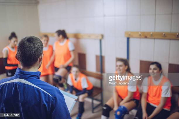 coach talking to a group of players - high school volleyball stock photos and pictures