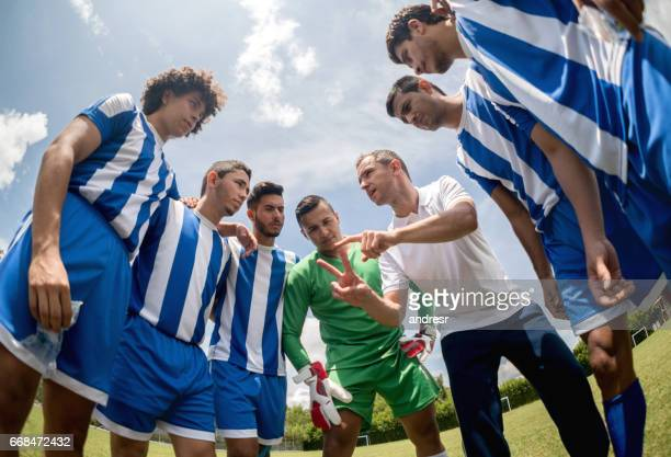 coach talking to a group of soccer players - coach stock pictures, royalty-free photos & images
