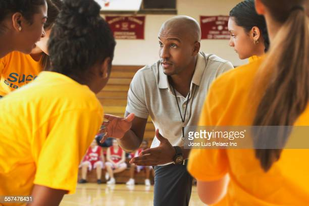 Coach talking to basketball team during game in gym