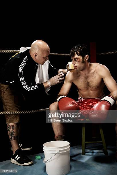 Coach talking to boxer in corner of boxing ring