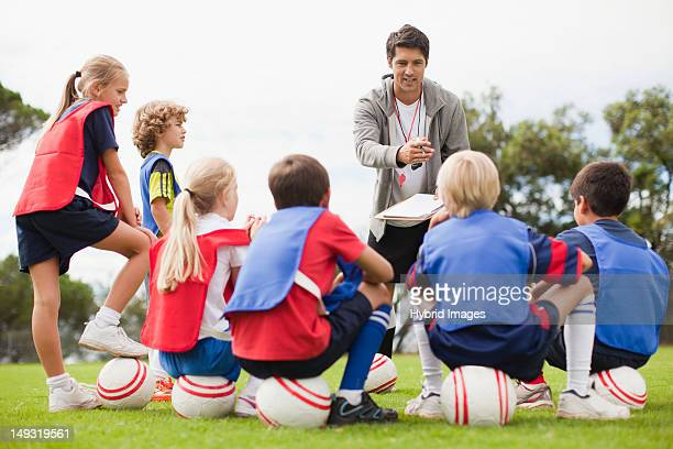 Coach talking to childrens soccer team