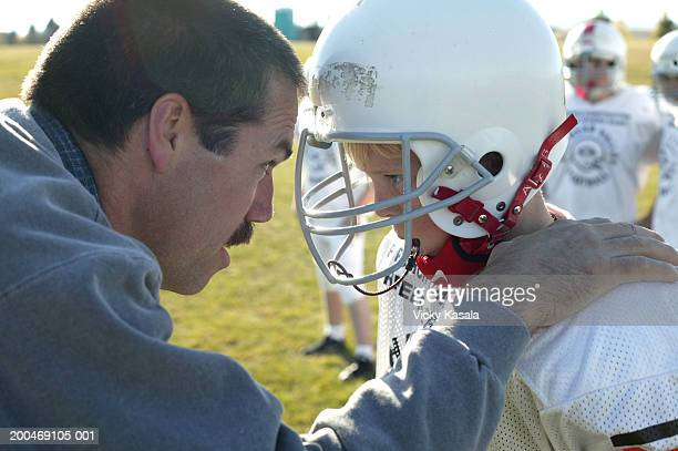Coach talking to football player (10-12) on sideline, side view