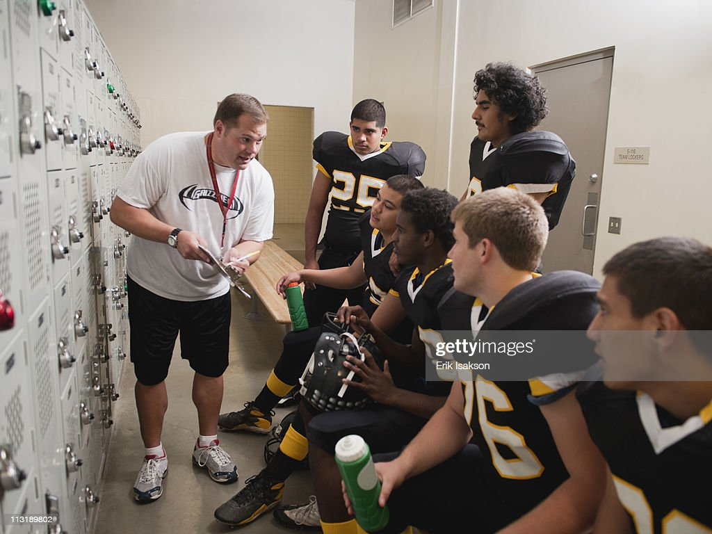 Coach talking to football players in locker room : Stock Photo