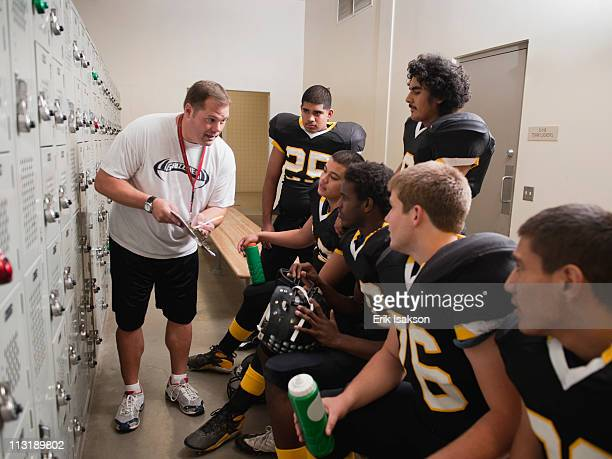 coach talking to football players in locker room - young boys changing in locker room stock pictures, royalty-free photos & images