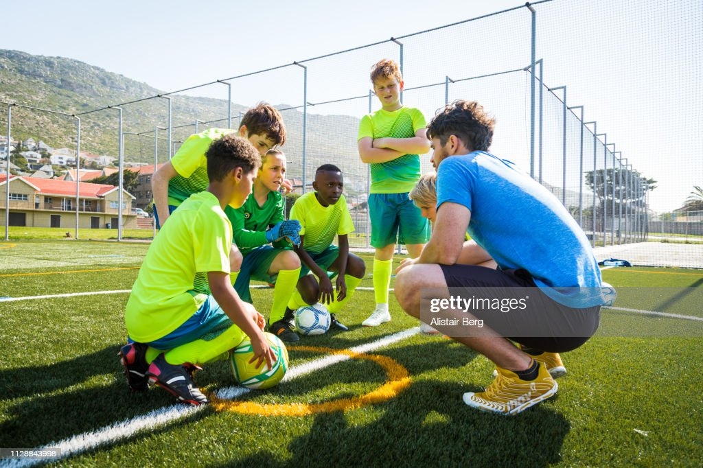 Coach talking to soccer players : Stock Photo