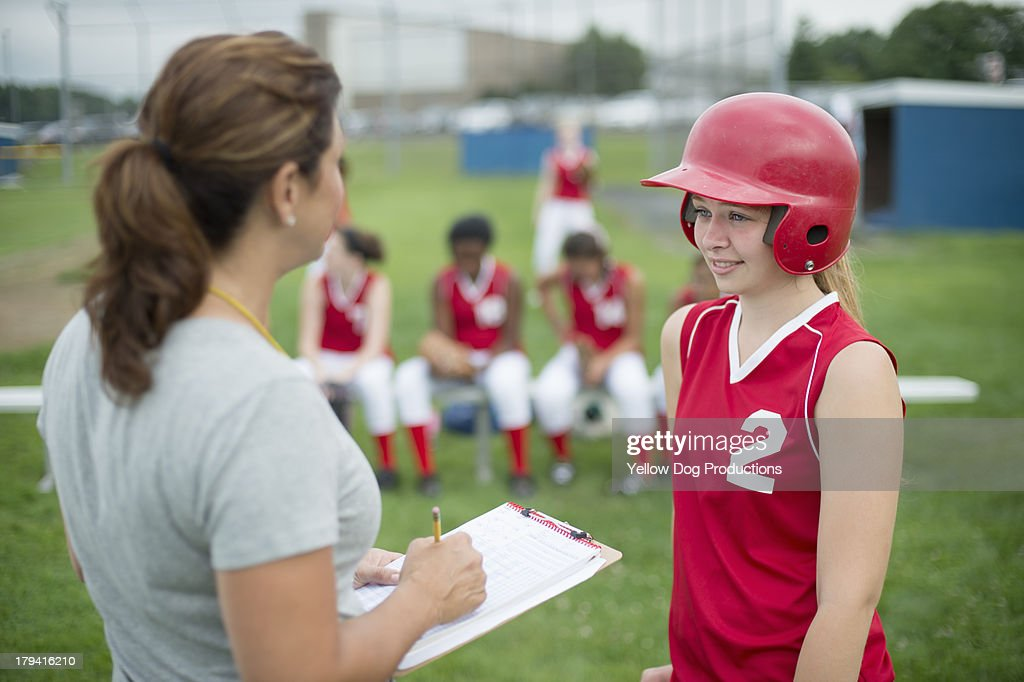 Coach Talking to Softball Player, teammates behind : Stock Photo