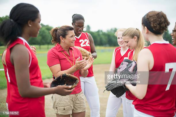 coach  talking to softball players - softball sport stock pictures, royalty-free photos & images