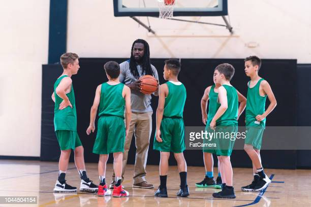 coach talking with his elementary boy's basketball team - sports training camp stock pictures, royalty-free photos & images