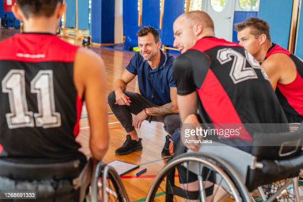 coach talking with wheelchair basketball players in gym - competition group stock pictures, royalty-free photos & images