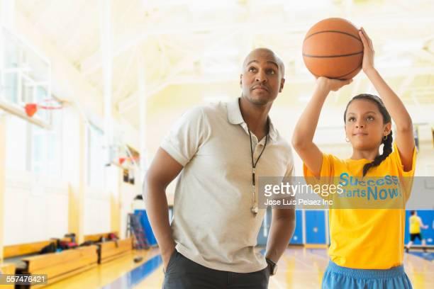Coach teaching basketball player in gym