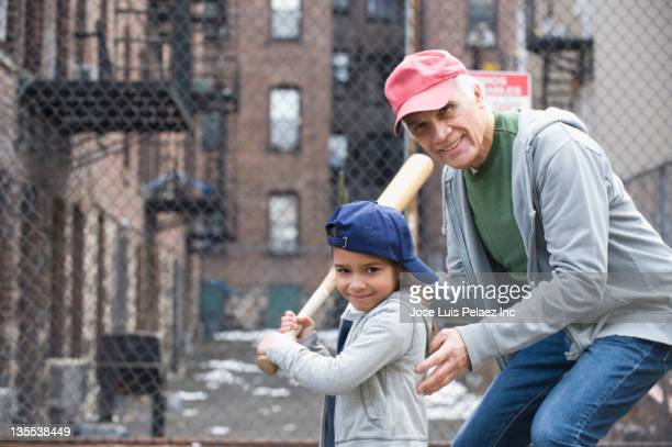 coach teaching girl to play baseball - batting sports activity stock pictures, royalty-free photos & images