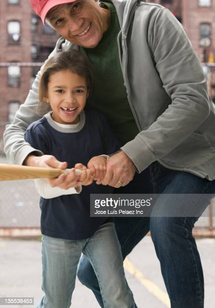 coach teaching girl to play baseball - batting sports activity stock photos and pictures