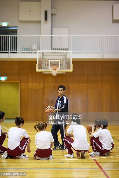 Coach teaching students (15-18) how to play basketball in school gym