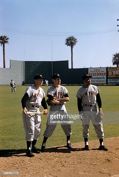 Coach Tom Henrich infielder Eddie Bressoud and outfielder Willie Mays stand along the dirt edge of the infield during batting practice prior to a...
