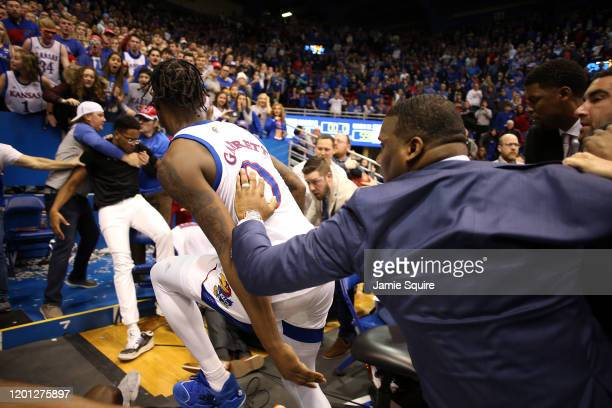 A coach tries to stop Marcus Garrett of the Kansas Jayhawks as James Love III of the Kansas State Wildcats falls backwards into fans during a brawl...