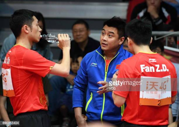 Coach Wang Hao speaks to Xu Xin of China and Fan Zhendong of China during Men's Doubles first round match on day 2 of 2017 World Table Tennis...