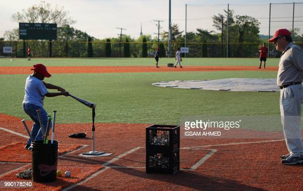 A coach watches children practice their baseball skills at the Nationals Youth Baseball Academy in Washington DC on May 7 2018 On a searing hot...