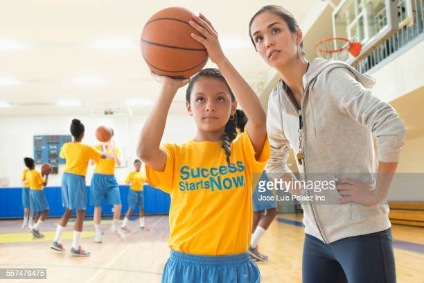 Coach watching basketball player during practice in gym